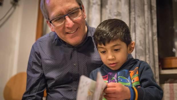 Khairi mit Lieblingspulli und Bilderbuch bei einem Besuch von Gammel in der Unterkunft in Nürnberg