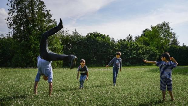 Dr. Andreas Gammel spielt mit den Kindern auf dem Rasenstück vor dem Flüchtlingsheim in Konstanz.