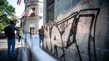"""""""Nazi-Kiez"""" steht an einer Wand, gegenüber eines Hauses, an dem Reichsflaggen aus den Fenstern hängen"""