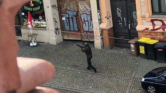Einer der Täter hält sein Gewehr im Anschlag. Er trägt Helm und Tarnkleidung