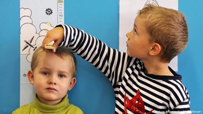 Kinder mit Messlatte Neu