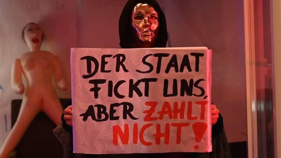 """Eine Prostituierte hält in der Herbertstraße ein Schild mit der Aufschrift """"Der Staat fickt uns, aber er zahlt nicht""""."""