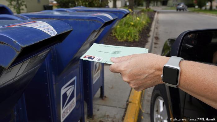Ein Mann wirft Post in einen US-Briefkasten