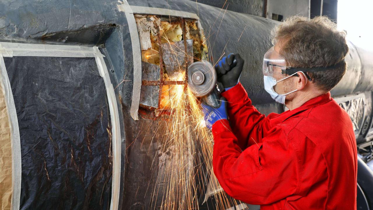 """Der """"Seehund""""-Experte flext den Rost an Metallstreben einer Öffnung im Zusatztank ab"""