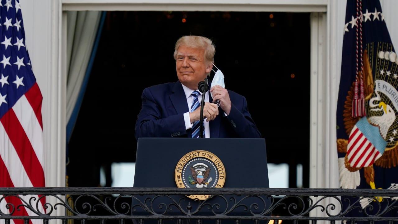 USA, Washington: Donald Trump, Präsident der USA, steht auf dem Balkon des Weißen Hauses und nimmt seinen Mund-Nasen-Schutz ab, um zu seinen Unterstützern zu sprechen, die sich auf dem Südrasen versam