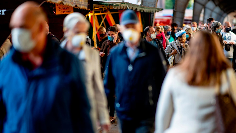 Menschen tragen auf einem Hamburger Wochenmarkt zum Schutz vor dem Coronavirus eine Mund-Nasen-Schutz