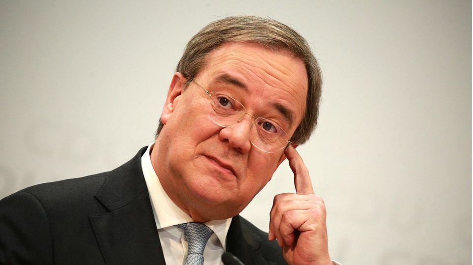 Ein Mann mit schwarz-grauem Seitenscheitel und randloser Brille legt den Kopf schräg und kratzt sich an der linken Schläfe
