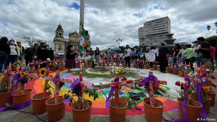 Auf einem Platz in Guatemala-Stadt stehen rund um einen mit Regenbogenfarben gestalteten Kreis kleine roten Blumentöpfen, in denen Sonnenblumen wachsen und in die rote Kreuze gesteckt sind. Proteste gegen Gewalt gegen Frauen in Guatemala.
