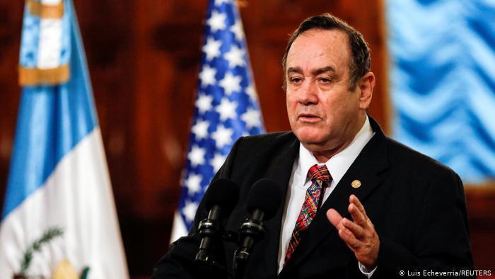 Guatemalas Präsident Alejandro Giammattei steht hinter zwei Mikrofonen und spricht