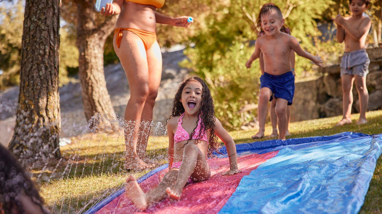 Kindergeburtstag Spiele: Mädchen schliddert im Garten über eine Wasserrutsche
