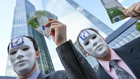 Zwei Männer mit Masken halten vor der Deutschen Bank Geldscheine in die Höhe.