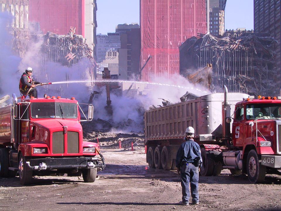 Ein Arbeiter sitzt auf einem Tankwagen und löscht den aufsteigenden Staub aus dem Schutt
